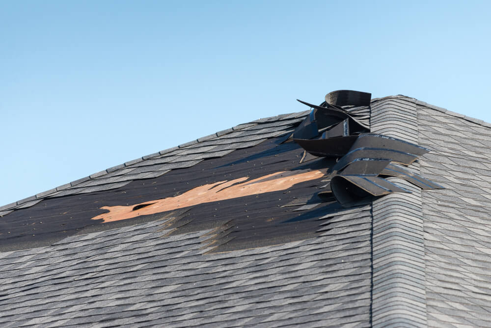 Home roof with wind damaged shingles after storm